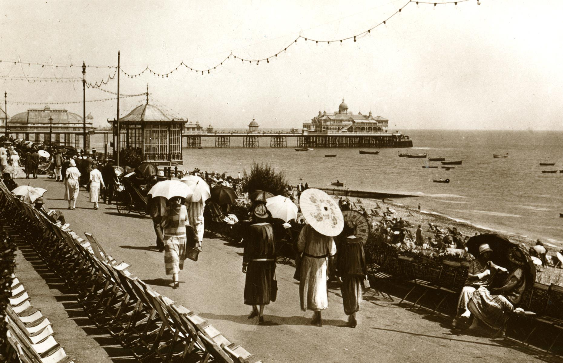 Slide 25 of 35: As train services poured passengers into Britain's seaside towns, the post-war and post-pandemic years saw major investments along the UK's coast. Previously neglected spots such as Eastbourne and Blackpool were transformed into glittering seaside resorts with hotels and amusement-packed beaches. Vacationers are seen here in the 1920s, wandering Eastbourne's ocean promenade, its pier rising in the background.