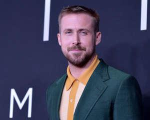 Ryan Gosling v obleku a kravatě se usmívá a dívá se do kamery