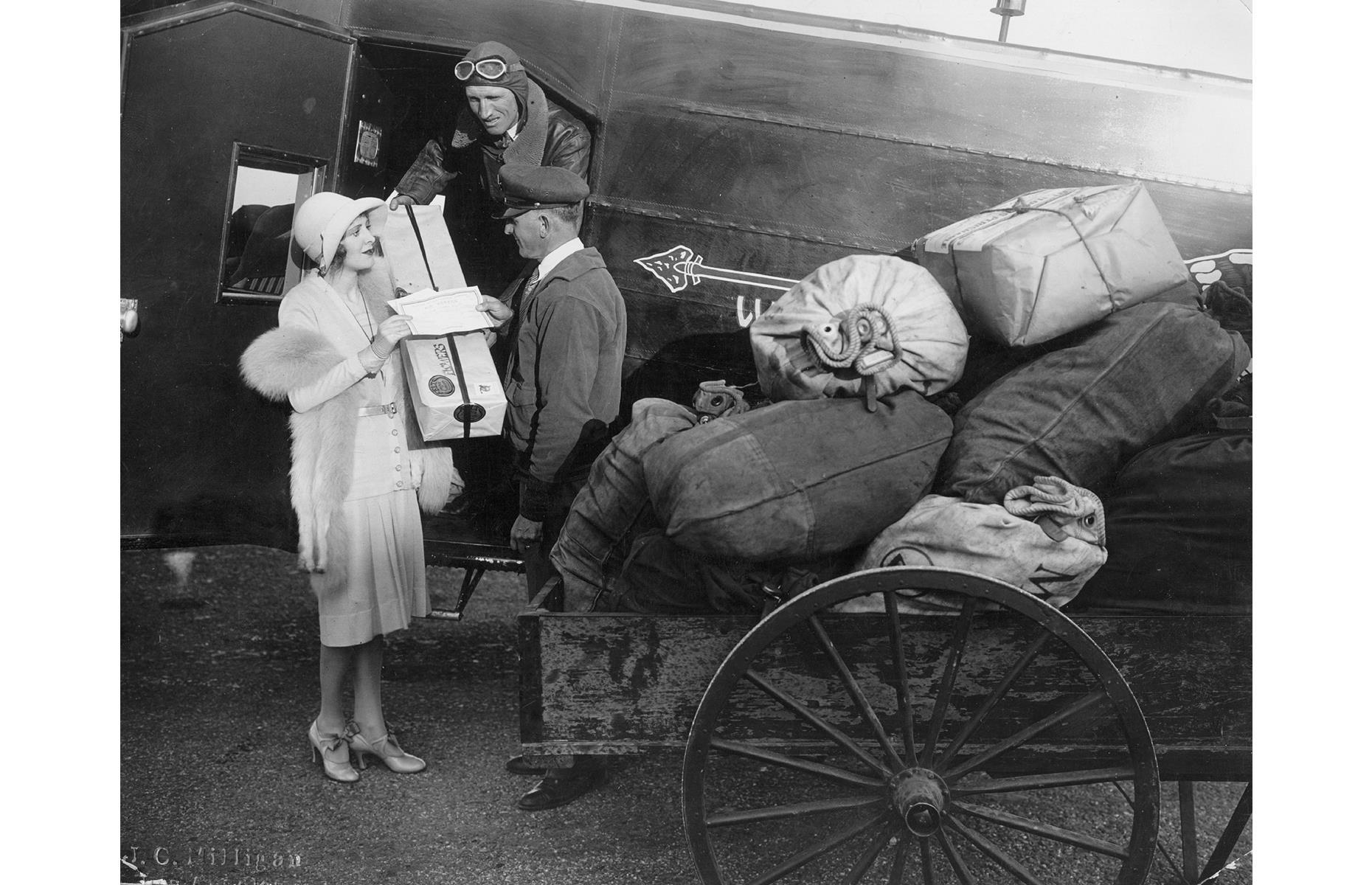 Slide 13 of 35: In the early days of the US air transport network, these new-fangled aircraft generally carried mail rather than passengers. This photo shows a woman handing her mail to aircraft crew employed by Western Air Express (later known as Western Airlines).