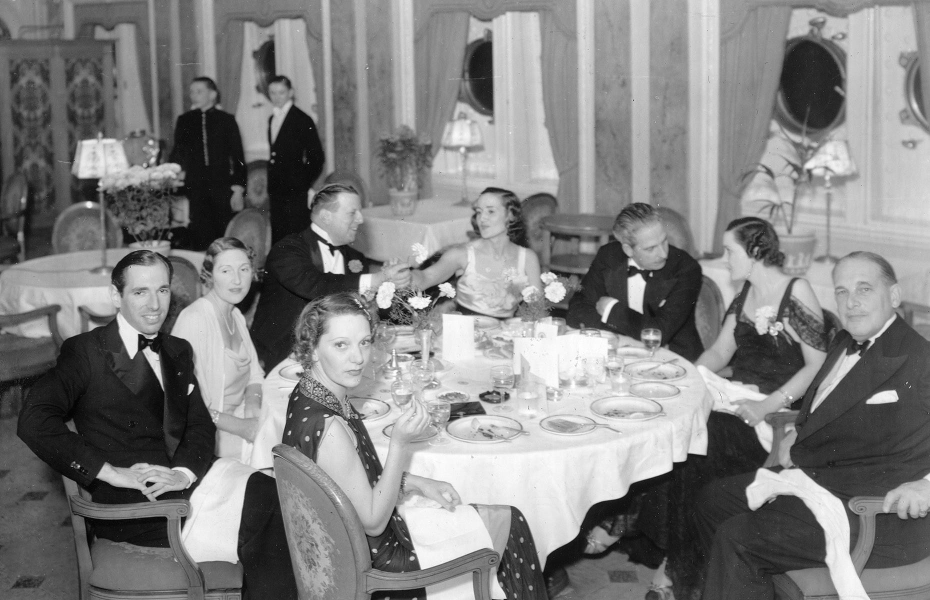 Slide 18 of 35: Cruise liners competed to win the Blue Riband title for the shortest Atlantic crossing time through the 1930s, and the RMS Queen Mary forged her way from Southampton to New York in just five days. Here a star-studded group, including performer Gertrude Lawrence, dine on the ship in early 1939.