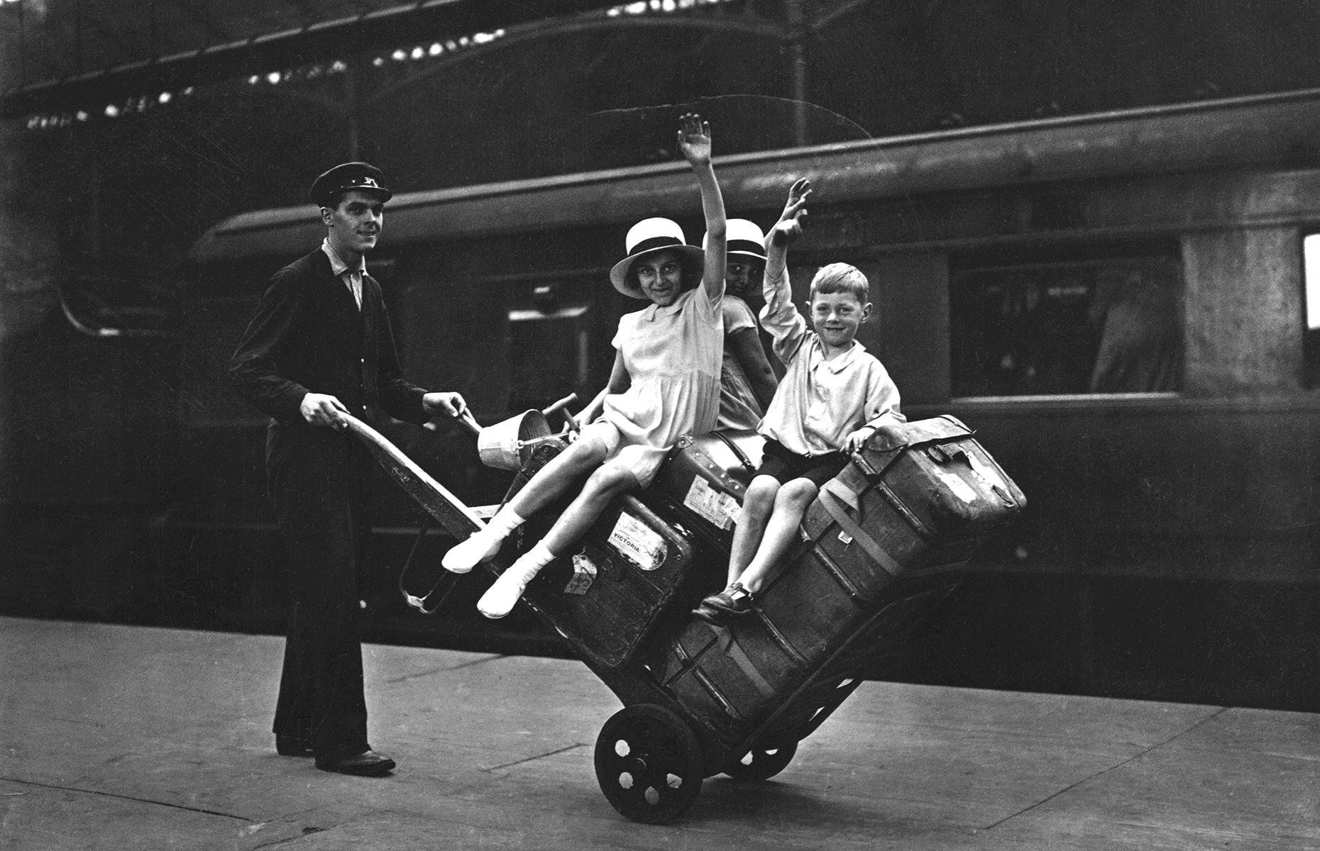 Slide 23 of 35: The ease and efficiency of a journey on the British railway meant that more families (especially those who couldn't afford a motor car) were able to enjoy short breaks and leisure excursions around the country. Here a group of delighted young vacationers enjoy a ride on a luggage cart at Euston station.