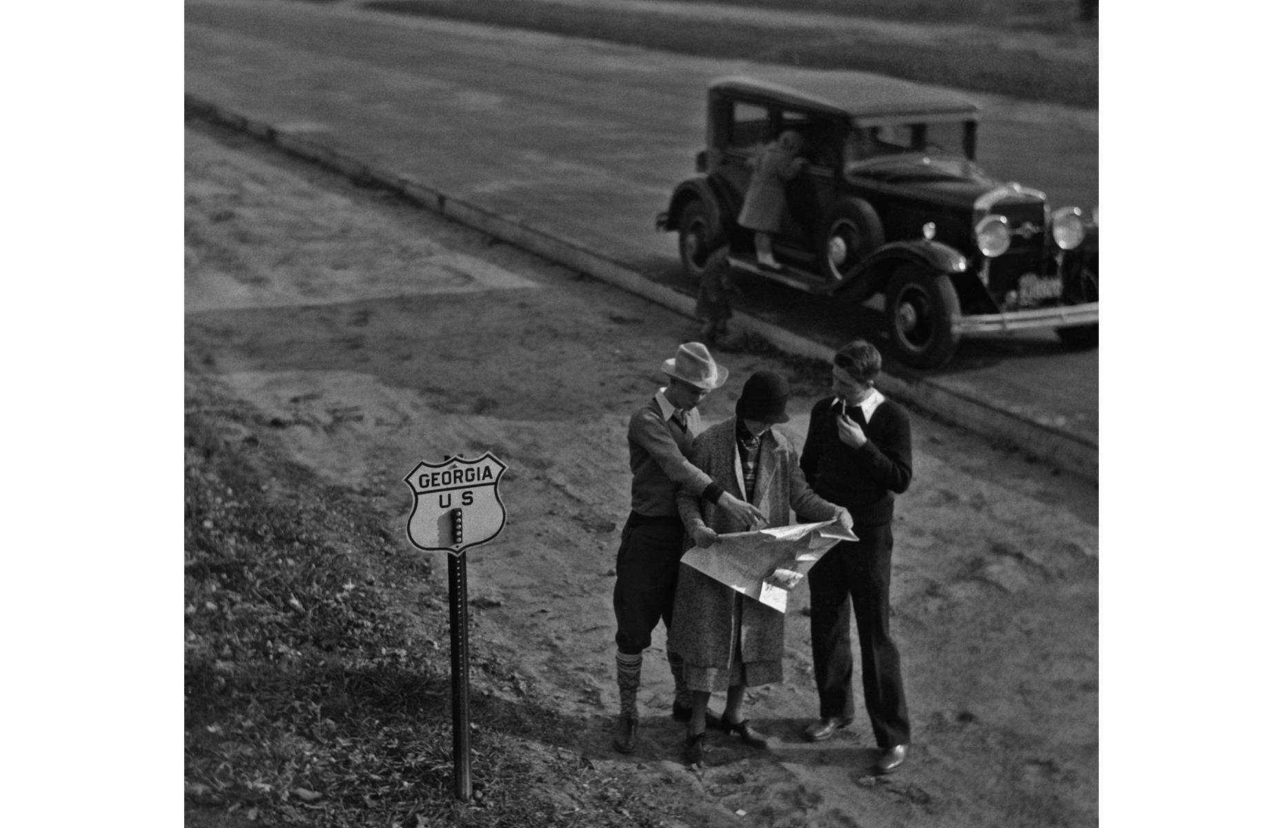 Slide 31 of 35: Road conditions improved dramatically in the United States through the 1920s and 1930s, and motorways were built across the country, as well as in European destinations such as Germany. The UK also invested heavily in dual-carriageway roads. Here, a young group of road-trippers in the US state of Georgia consult a map at the side of the highway in the 1930s.