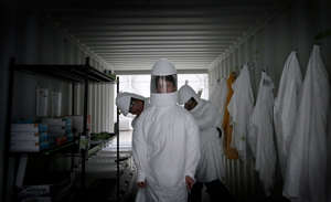 a man standing in a room: Ryan McCarthy of Battelle Critical Care Decontamination System gets suited up to decontaminate used personal protection equipment from El Paso area hospitals Friday, July, 17, 2020. The company is based in a hangar at the El Paso International Airport.