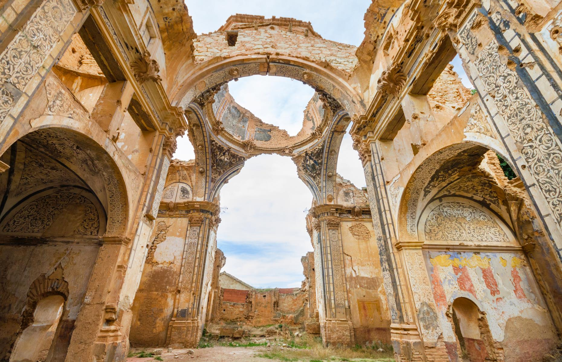 Slide 19 of 64: Piles of rubble still sit among the crumbling walls which are scarred with bullet holes and bleached by the sun – and now weeds are forcing their way into the cracks and crevices too. Tourists can usually visit Belchite on an organized tour during the day or after sunset.