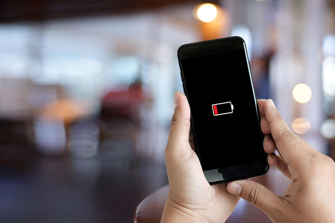 a hand holding a cellphone: Your smartphone's battery lifespan depends on many factors, including extreme temperature fluctuations and your charging habits.