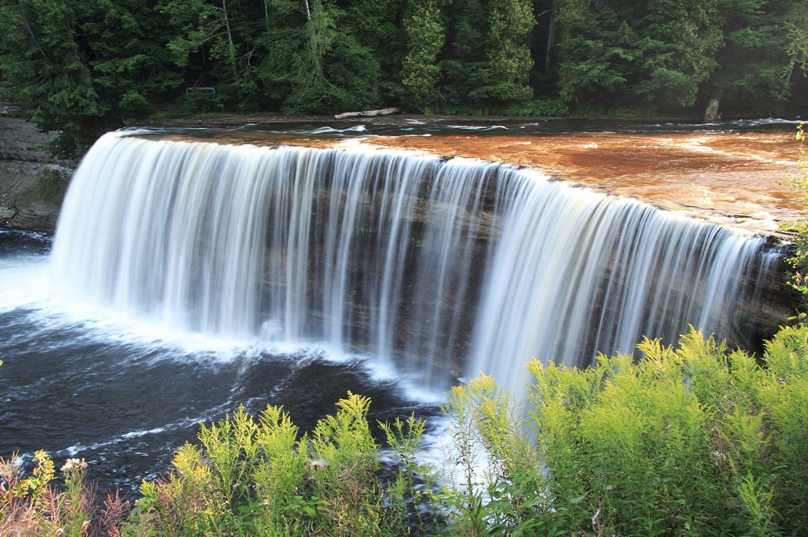 Slide 23 of 53: Located in Northern Michigan, Tahquamenon Falls State Park sits close to the border of Canada. Found along the Tahquamenon River, this park is known and named for the powerful waterfalls found in the area, which provide ample opportunity for photography.Fishing, canoeing, hiking and picnicking are also popular activities for visitors to Tahquamenon Falls. You can take your time exploring the park by renting out an available cabin or lodge or camping in the designated campgrounds.