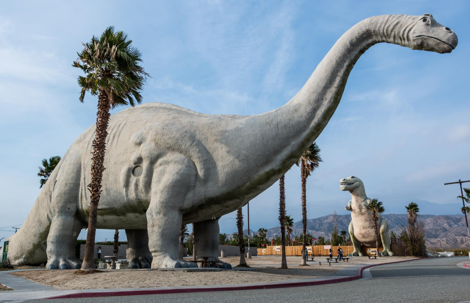 Slide 11 of 101: The drive from city to city takes around one hour 45 minutes, but attractions en route tend to slow travelers down. There's the Cabazon Dinosaurs (pictured), a quirky roadside amusement famed for its giant robotic dinosaurs. There's also the San Gorgonio Pass, a particularly striking stretch of roadway with mountain views and a large wind farm. Palm Springs itself is famed for its resorts and its panorama-wielding aerial tramway (the tramway is temporarily closed – have a look at the website for updates).