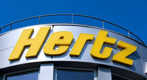 a sign above a store: Hertz (HTZGQ) sign in Montevrain, France on May 8, 2016.