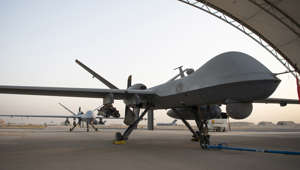 a large passenger jet sitting on top of a runway: A pair of MQ-9 Reapers from the 46th Expeditionary Attack Squadron are parked on the flightline at Ali Al Salem Air Base, Kuwait, June 9, 2020.