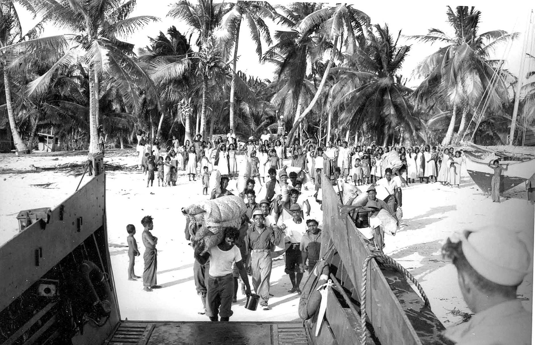 Slide 25 of 35: The islanders were evacuated (pictured here) but they were sadly never able to come back. Bikini Atoll's groundwater and soil became contaminated during the tests and it was not safe for the island's original residents to return home. Today the atoll's corals and marine life are showing signs of recovery and a few caretakers work on the island (though they must bring food and water provisions with them from elsewhere). The atoll remains otherwise deserted.