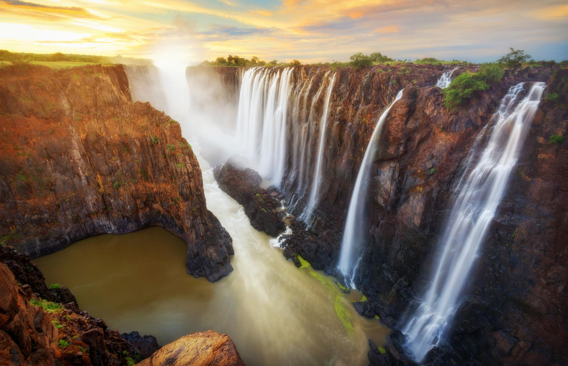 Slide 10 of 30: However you look at it, this huge, thundering waterfall on the Zambezi River is pretty incredible. Straddling Zimbabwe and Zambia, with cascades more than 5,500 feet (1,700m) wide and 355 feet (108m) tall, it's one of the world's largest and most iconic waterfalls. It's also among the loudest, making such a racket and creating such a cloud of mist that the Kalolo-Lozi people named it Mosi-oa-Tunya, or 'The Smoke That Thunders'.