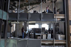 People stand inside a damaged building near the site of an explosion on Tuesday that hit the seaport of Beirut, Lebanon, Thursday, Aug. 6, 2020. The blast which appeared to have been caused by an accidental fire that ignited a stockpile of ammonium nitrate at the port, rippled across the Lebanese capital, killing at least 135 people, injuring more than 5,000 and causing widespread destruction. (AP Photo/Bilal Hussein)