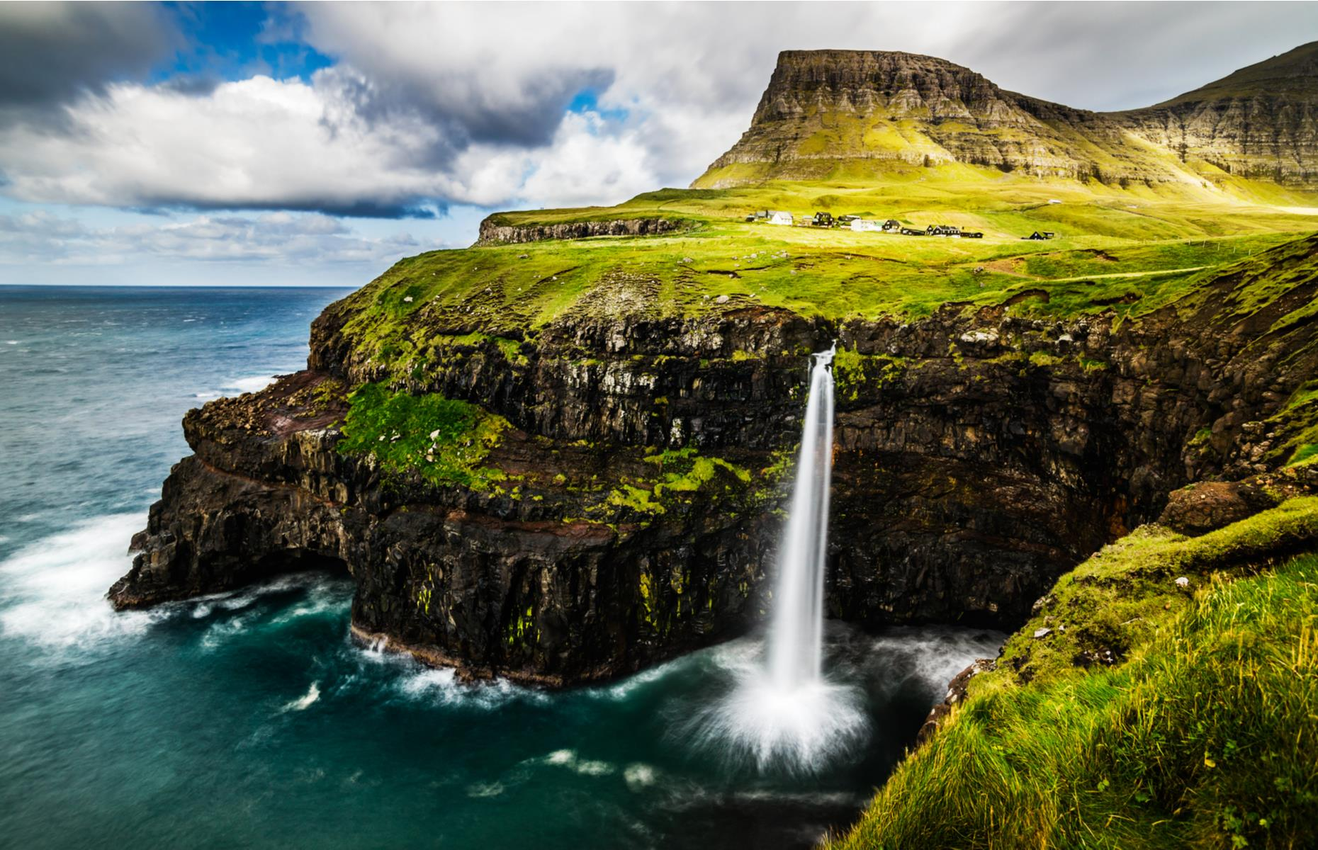 Slide 11 of 31: Every inch of the Faroe Islands archipelago feels otherworldly, from the green-carpeted mountains to Nordic villages and fjords shrouded in cool mist. One of the most dramatic sights is on Vágar, one of the largest islands. Here, Múlafossur waterfall drapes from a verdant, clifftop perch, emptying into the sea like white velvet.