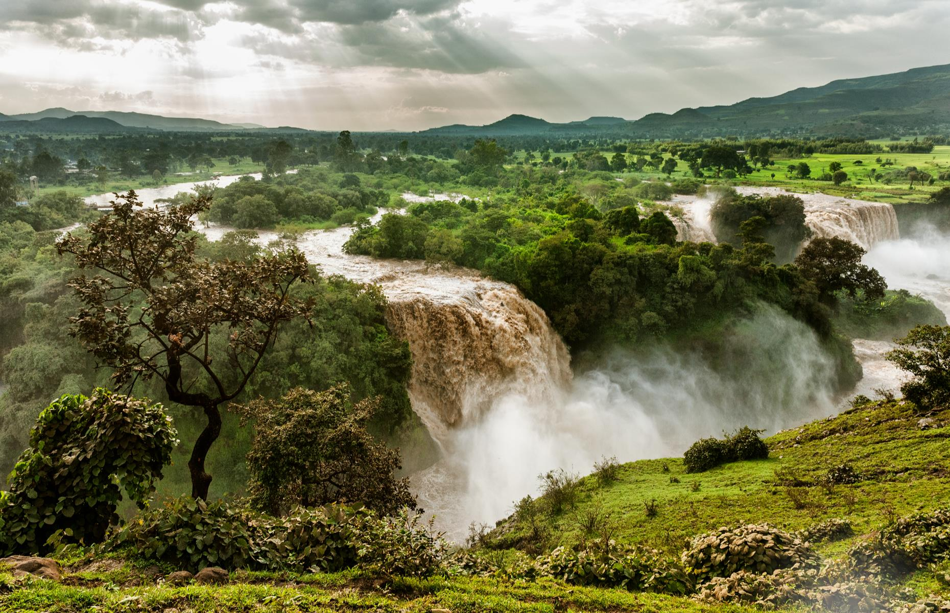 Slide 18 of 31: The mist produced by the Blue Nile Falls in northwestern Ethiopia is so dense, the waterfall's local name is Tis Abay – Amharic for 'great smoke'. Straddling the White and Blue Nile rivers, its biggest drop is around 140 feet (43m) and its widest point is 1,312 feet (400m), creating a dramatic sight amid lush rainforest.