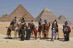 a group of people riding on the back of a horse: This picture taken on March 25, 2018, shows tourists in front of the Giza pyramids complex, on the southwestern outskirts of the Egyptian capital Cairo. / AFP PHOTO / FETHI BELAID (Photo credit: FETHI BELAID/AFP/Getty Images)