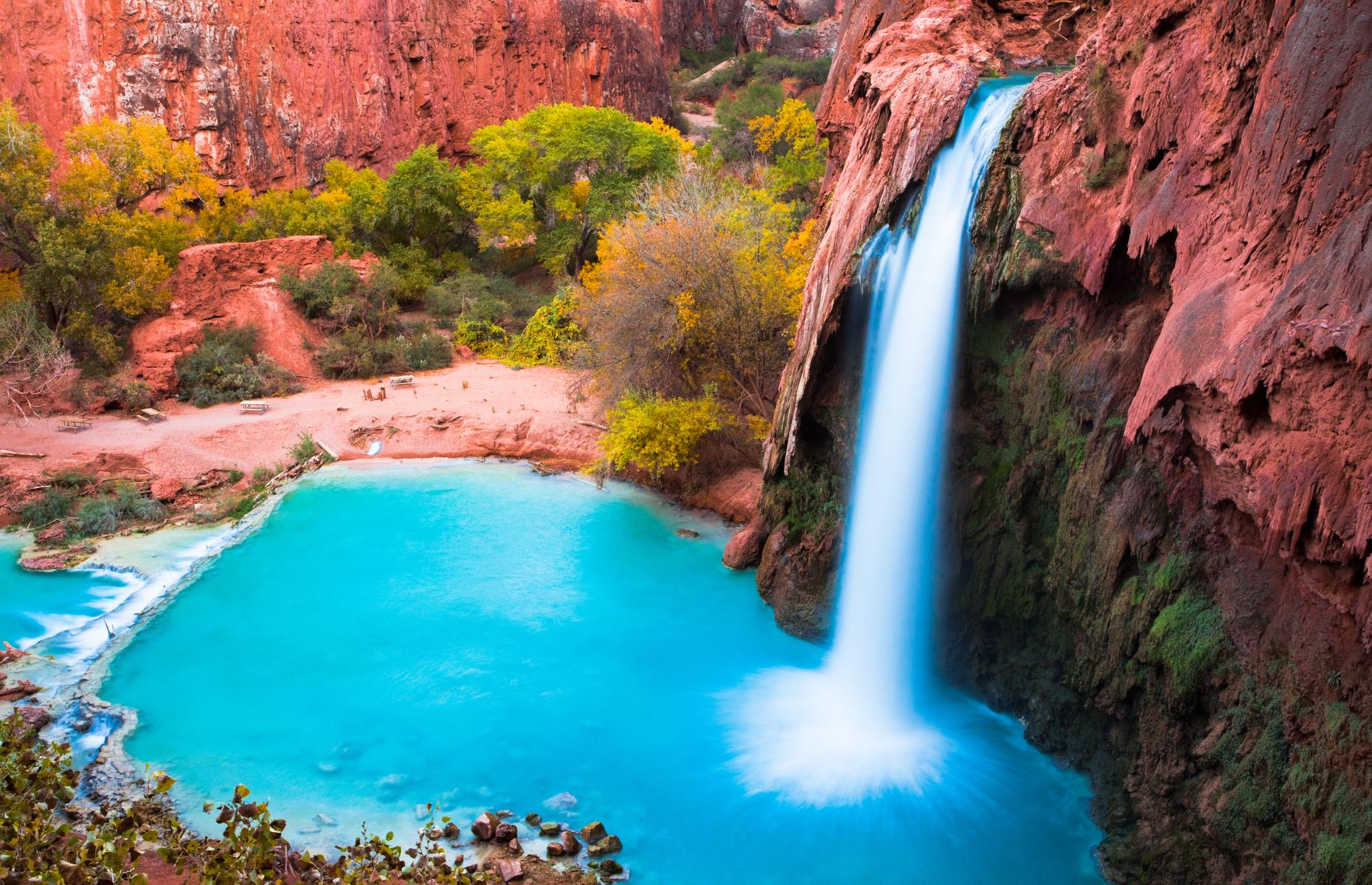 Slide 10 of 31: The colors of Havasu Falls look otherworldly but this eye-popping combination of orange-pink rock and a pool of cerulean blue, fed by a silken cascade, is definitely real. One of five waterfalls on the Havasupai Indian Reservation, within the Grand Canyon, the water owes its vibrant hue to calcium carbonate in the water. Take a look at more of America's most beautiful waterfalls here.