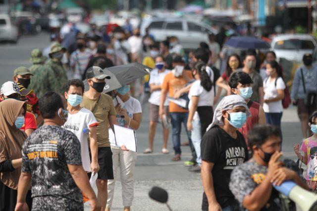 một nhóm người đi bộ xuống phố: Cư dân dọc Earnshaw St. ở Sampaloc , Manila vào thứ Tư, ngày 3 tháng 6 năm 2020 đổ xô đến một trung tâm y tế để tiến hành kiểm tra nhanh COVID-19, tận dụng các hạn chế được nới lỏng theo kiểm dịch cộng đồng chung. DANNY PATA