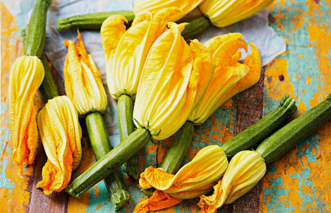 Slide 10 of 25: If you grow your own vegetables, you may recognize these bright yellow zucchini flowers which usually sprout during the summer months. But if you've been throwing them away, you've missed a trick. These delicate and slightly sweet tasting flora are delicious when stuffed with ricotta and deep-fried.