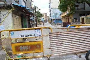 a truck is parked on the side of a building: Bangalore containment zones