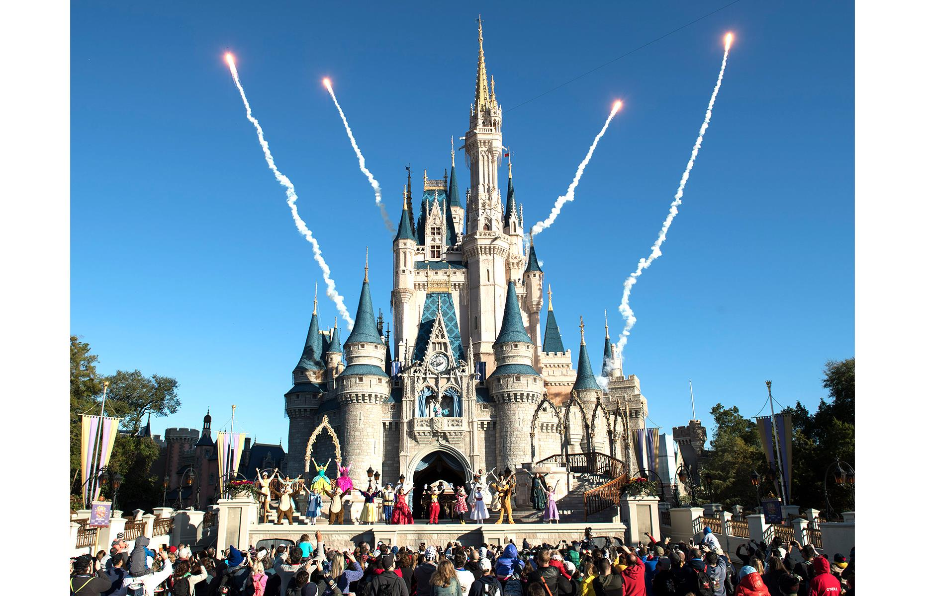Slide 28 of 31: The turrets and towers of Cinderella Castle preside over the Magic Kingdom, the backdrop for firework displays and performances by well-loved characters. You can usually wander within the castle all day (open but with limited admissions), but a secret suite, or 'royal bedchamber', means a lucky few get to overnight here too. The palatial suite is all stained-glass windows, intricately carved fireplaces and gold-patterned linens, and a stay is by invitation only. Now go back in time with historic pictures of Disney's parks.