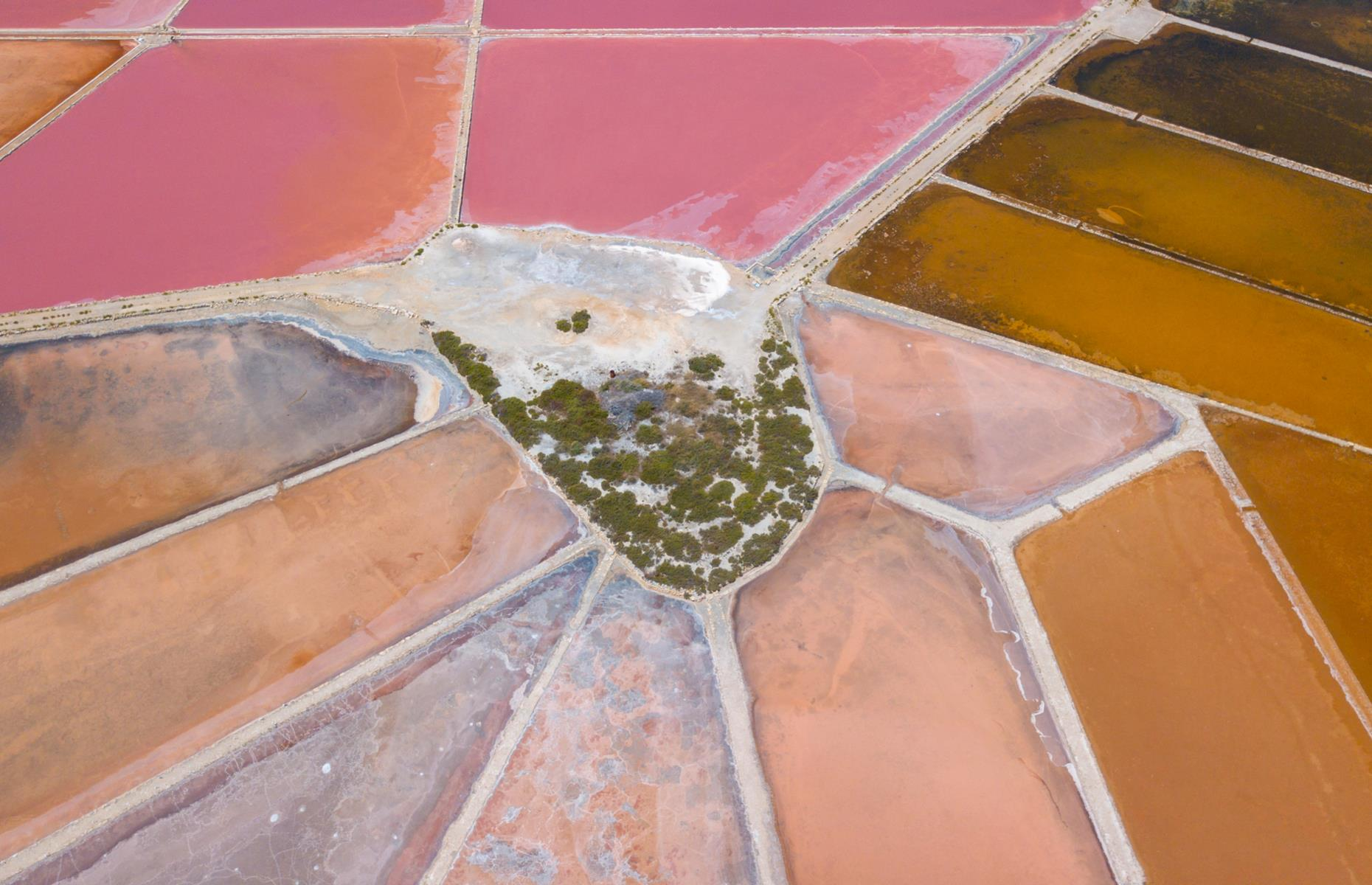 Slide 22 of 43: While it may look like a giant paint palette, this pink landscape is actually made up of salt flats and is situated in the seaside resort of Colonia de Sant Jordi in Mallorca's Ses Salines district. Salt is a major export here and a great source of local pride – a symbol of a salt mound even appears on the area's coat of arms. The colors (earthy pink, deep tan and rich nude) pop when captured from up high.