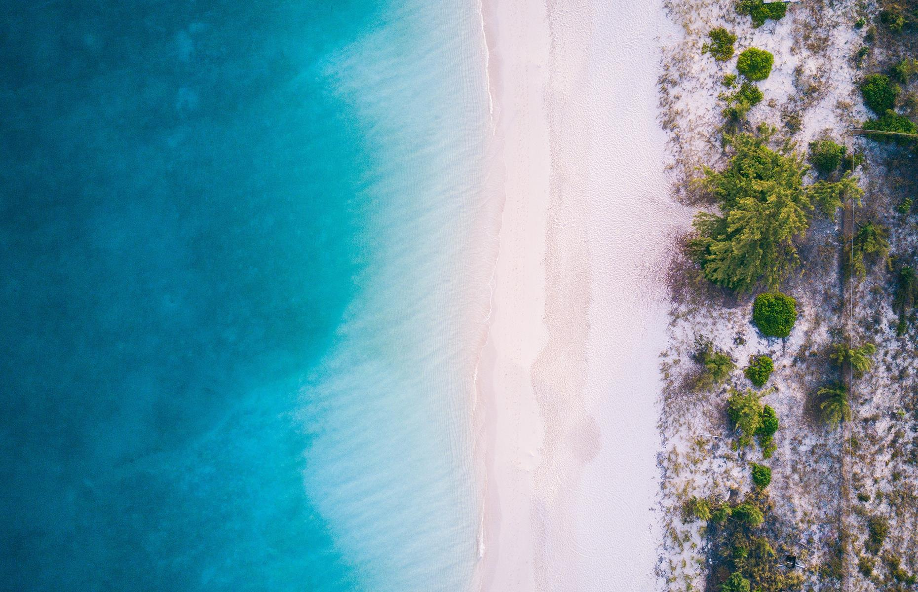 Slide 4 of 43: Calm, blue ocean and soft, white sands characterize Grace Bay on Providenciales (Provo), part of the idyllic Turks and Caicos archipelago. It's pristine and quiet, with colorful cays and marine life flourishing in the waters – the stillness here is captured from above.