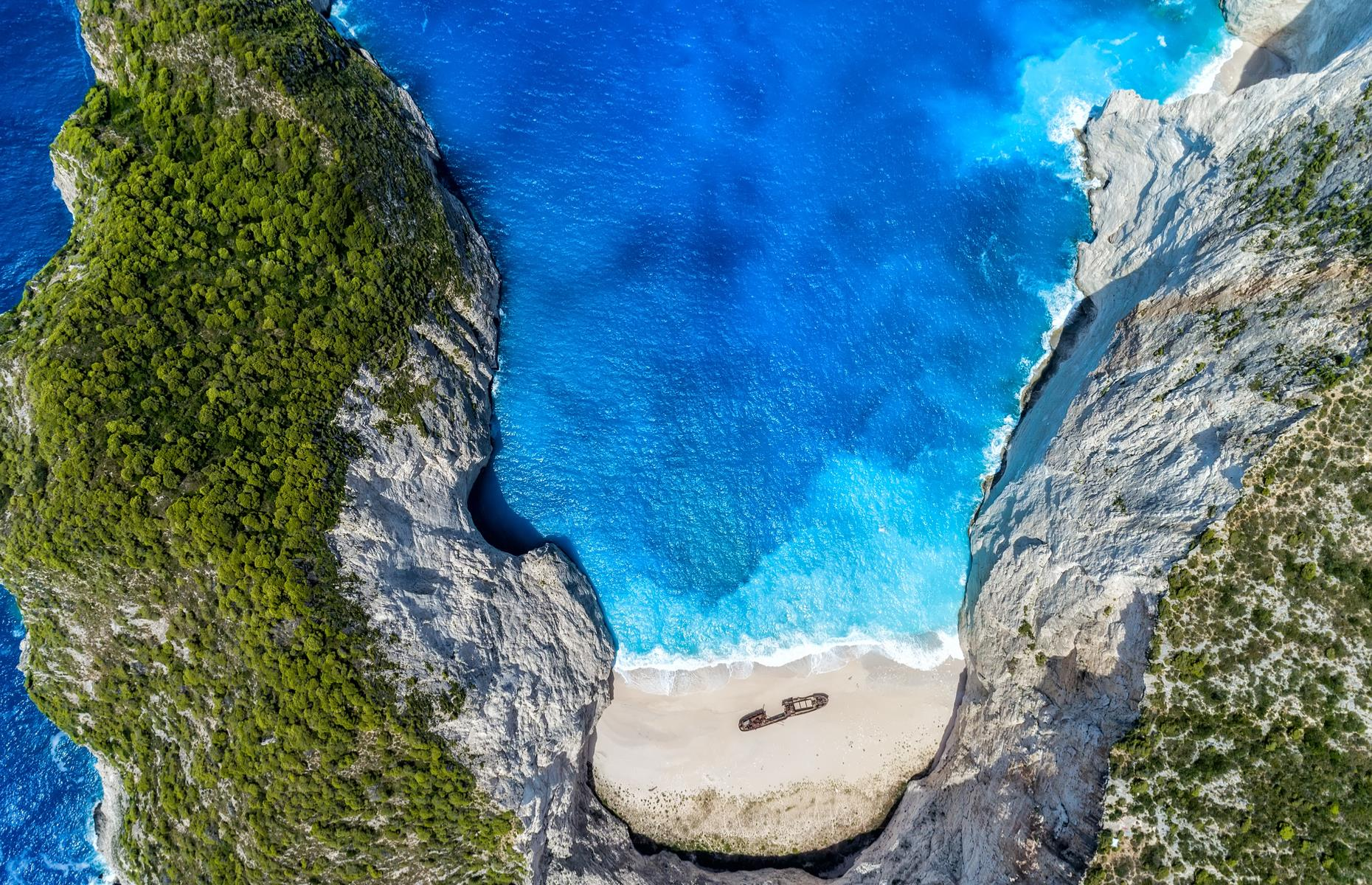 Slide 41 of 43: Green-topped cliffs, cobalt waters and pale gold sands characterize this strand on the Greek island of Zakynthos. But Navagio is best known for the ambient shipwreck settled on the sand, earning it the moniker of 'Shipwreck Beach'. Once sailed by smugglers, the ship is thought to have been washed up in the 1980s – here it appears as a mere speck on the sand, protected by arching limestone crags.