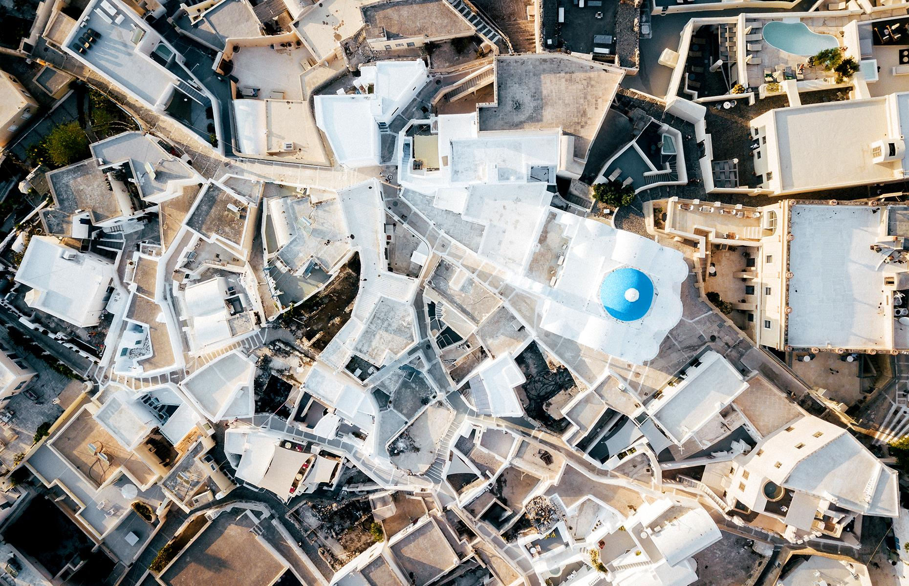 Slide 37 of 43: Santorini's sugar-cube buildings take on new life when seen from the air. Captured here is the village of Pyrgos Kallistis (better known as just Pyrgos) and the white-washed houses, labyrinthine passageways and contrasting blue domes appear like a geometric pattern.