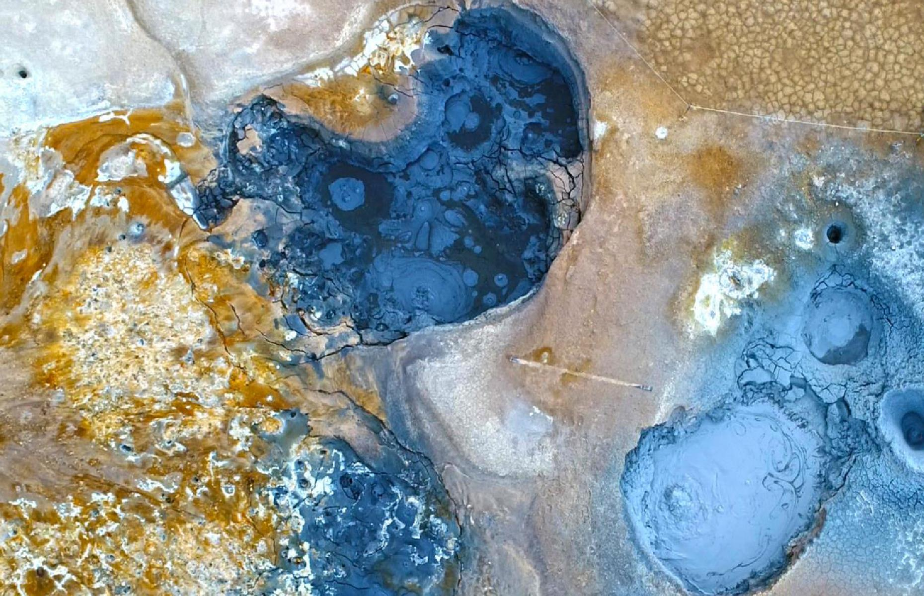 Slide 27 of 43: The Hverir Geothermal Area, part of North Iceland's so-called 'Diamond Circle', is a landscape filled with simmering mud pots and hissing hot springs. This eye-popping view from the sky shows the brilliant tones of blue and yellow, not too dissimilar to the USA's famous Grand Prismatic Spring.