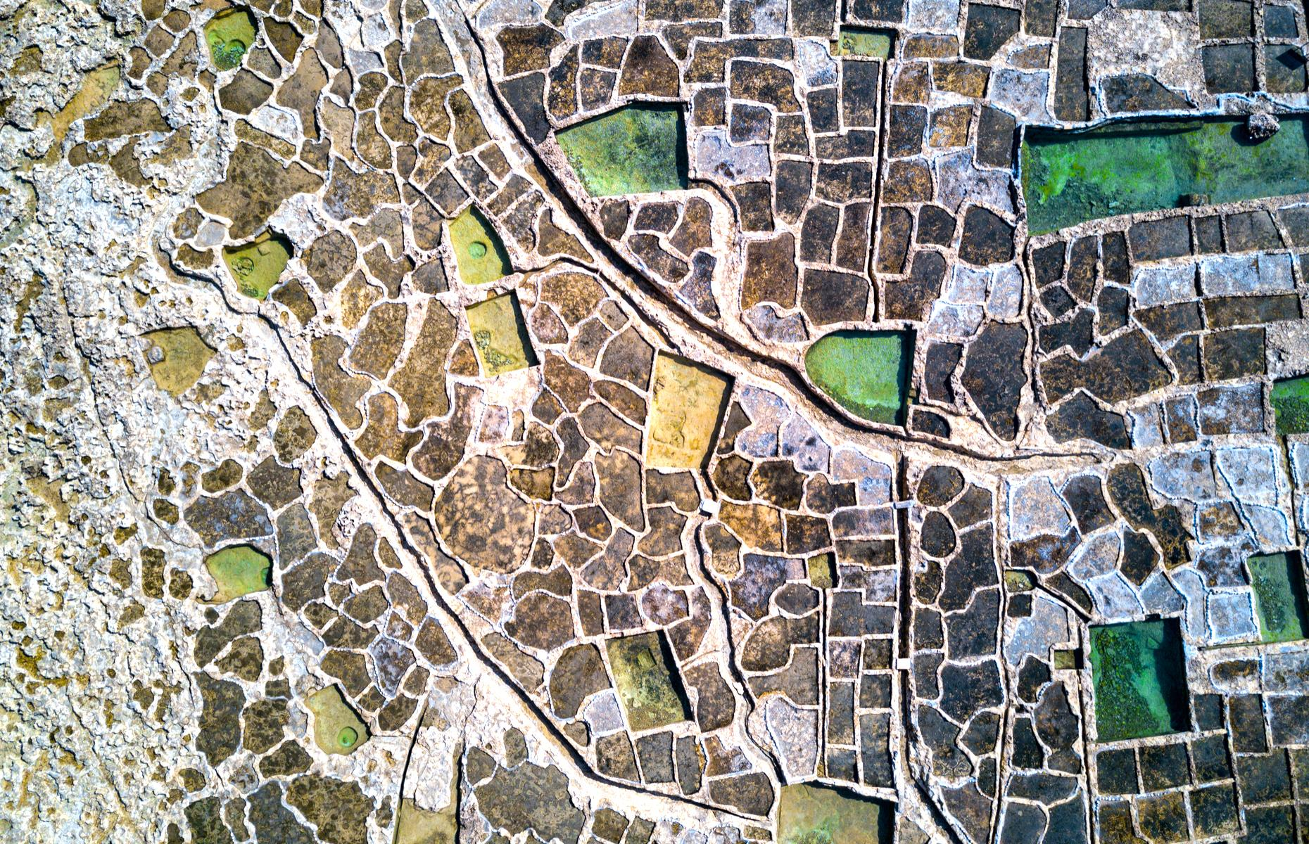 Slide 3 of 43: The pretty Maltese island of Gozo is famous for its salt production with large clusters of salt pans collecting on the north coast. From above, these pans appear like a mosaic with hues of earth brown, white and sand punctured by emerald-green water.