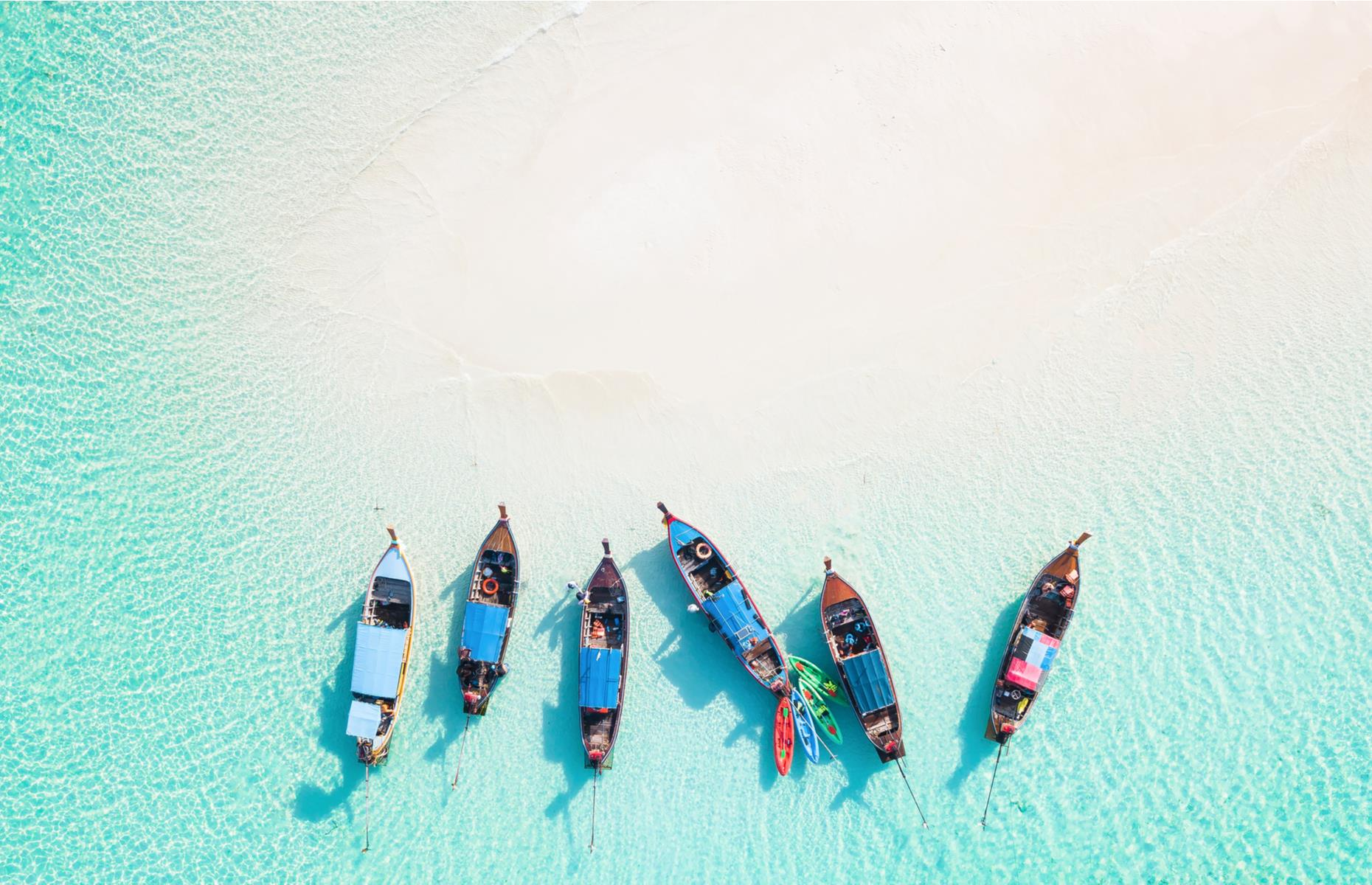 Slide 39 of 43: The Thai island of Koh Lipe floats in the Andaman Sea, fringed with sugar-white sands. From the sky you can appreciate the crystal clarity of its waters, dotted with colorful boats and filled with rich coral reefs.
