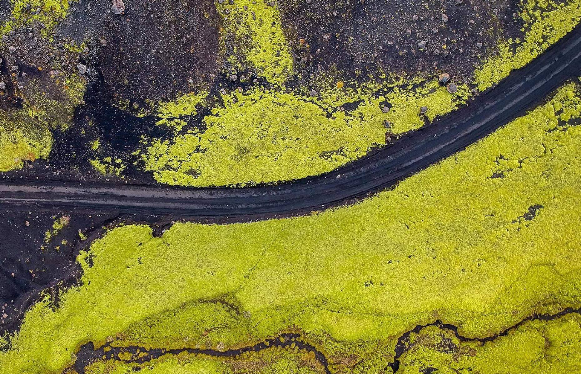 Slide 9 of 43: The Land of Ice and Fire is a stunner whichever way you look at it, but from above there's extra drama. This highland road slices through Iceland's Interior, not far from the volcanic fissure of Laki. A bird's-eye view shows how the lime-green moss contrasts with the ink black of the lava rocks.