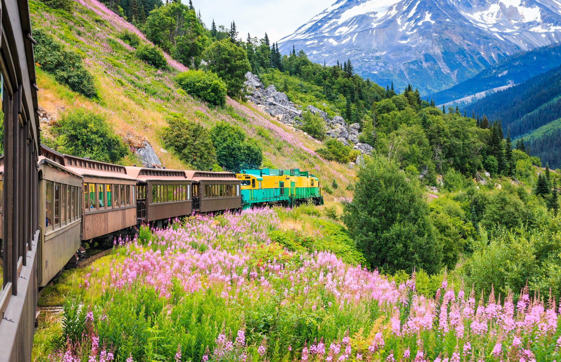 Slide 27 of 61: This railway route touts itself as the most scenic in the world, and it's not hard to see why. The snow-dusted mountains, pink and yellow wildflowers and rambling hills appear almost Alpine. The railroad, whose construction began in 1898, instead rattles through Alaska towards Canada, leaving from the little city of Skagway. The White Pass Summit Excursion is the most traditional of routes, a 40-mile (64km) jaunt taking in the teetering peak of its namesake mountain pass. Trips look set to return during the 2021 season, with booking essential.