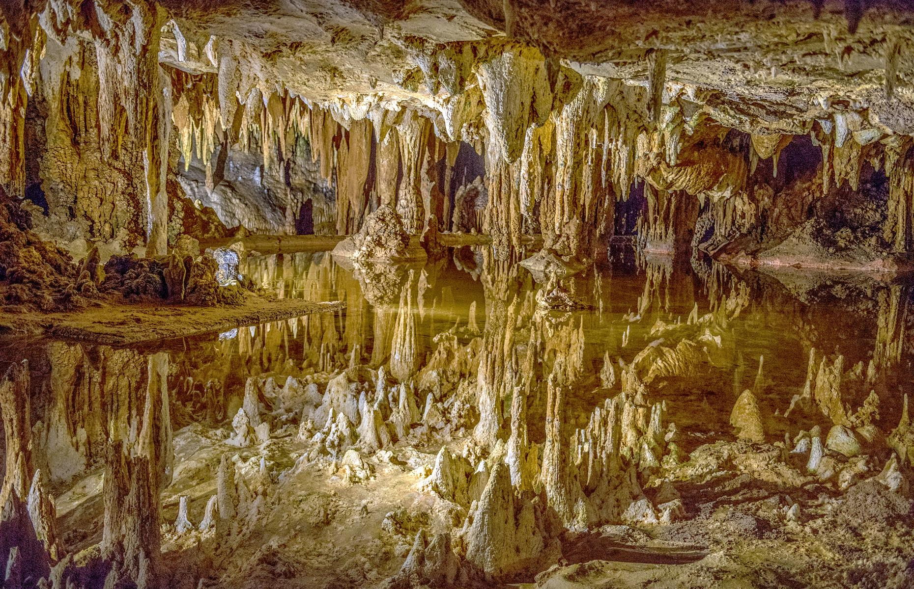 Slide 21 of 61: These otherworldly caverns, the most extensive in the eastern United States, open out below the Shenandoah Valley's Blue Ridge Mountains. The sand-colored stalagmites and stalactites have sprouted over millions of years, and winding tunnels give way to echoing chambers. Most fascinating of all is Dream Lake: its 20 inches of water look much deeper due to the reflections on its glittering surface. There's also an organ that uses the rock formations to make sweet music. The caverns have reopened with new COVID-19 measures in place for visitors.