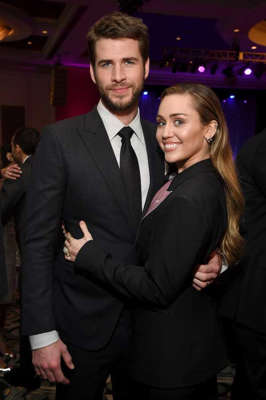 Miley Cyrus standing next to a man in a suit and tie: Miley Cyrus and Liam Hemsworth