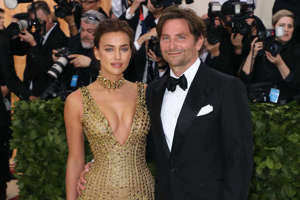 Irina Shayk et al. standing in front of a crowd posing for the camera: Bradley Cooper and Irina Shayk