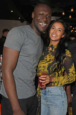 Stormzy, Maya Jama standing next to a person: Stormzy and Maya Jama