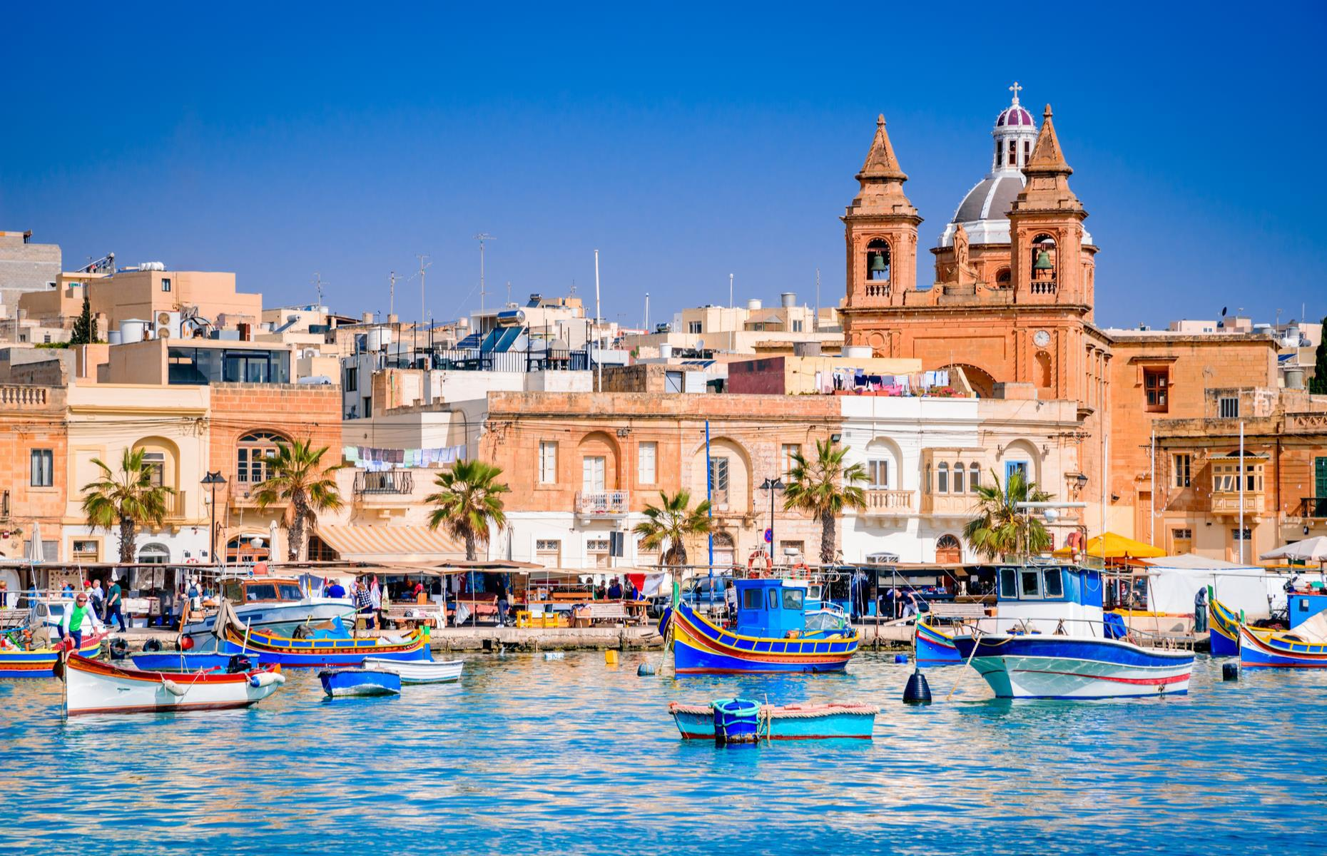 Slide 13 of 31: On Malta's southeast coast you'll find the fishing village of Marsaxlokk. Unlike most of Malta, it's virtually untouched by developers so life here is slow. Pictured is a fleet of traditional luzzu boats bobbing in the harbor.