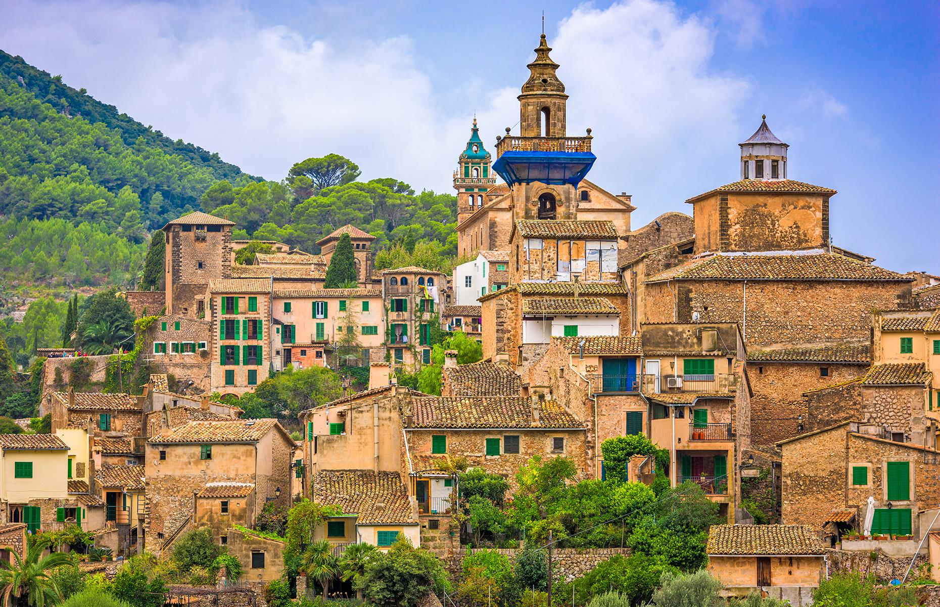 Slide 7 of 31: Nestled in the truly picturesque valley of the Tramuntana mountains, Valldemossa is one of Mallorca's most idyllic spots. An area of outstanding beauty, the village's sun-bleached stones stand out against the green farmlands and forests around it.