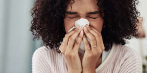 a woman eating a sandwich: Your allergies may get worse in the fall thanks to seasonal allergens like ragweed pollen. An allergist explains fall allergy symptoms, and how to treat them.
