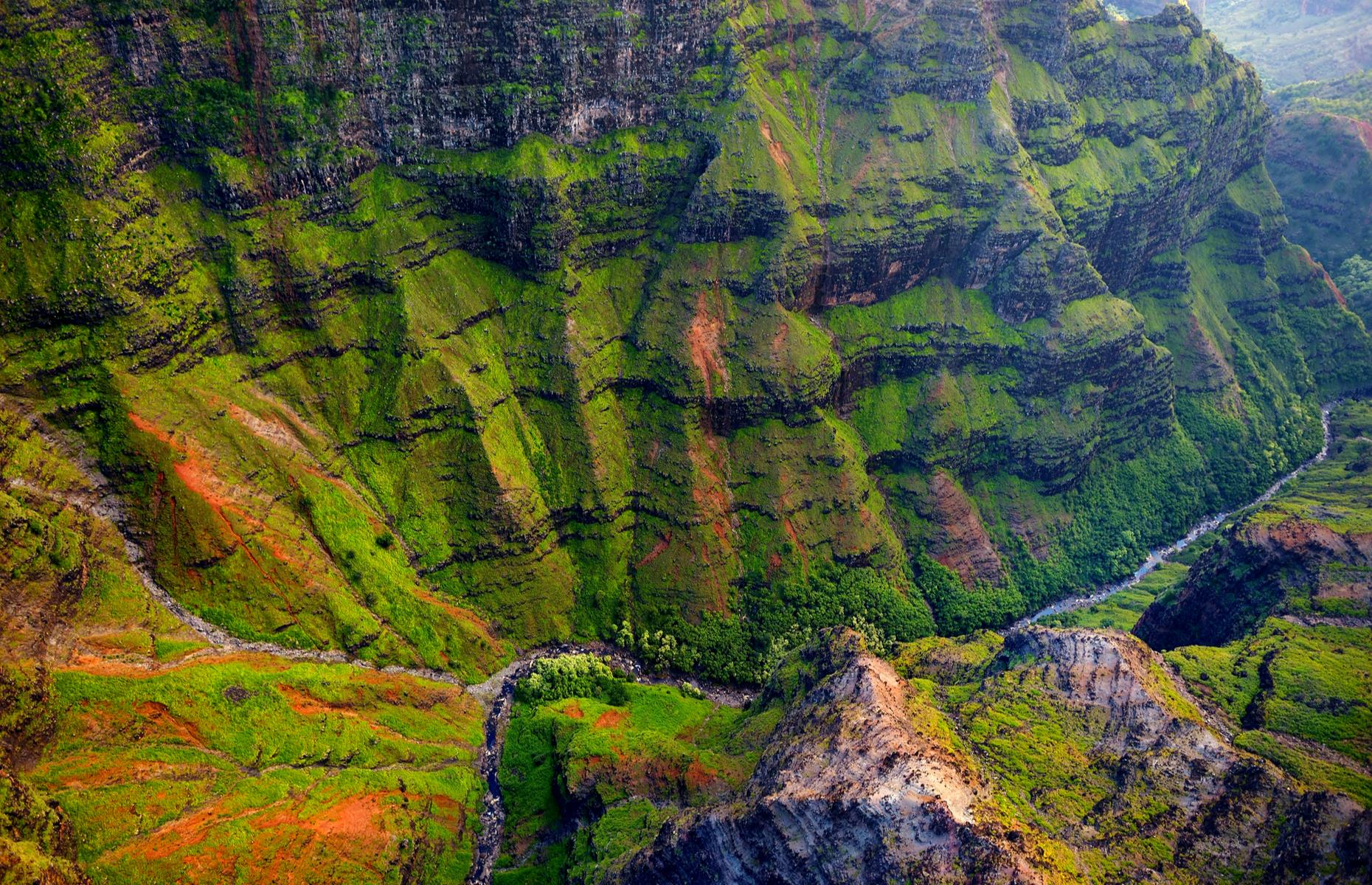 Slide 14 of 31: If you're visiting Hawaii, Waimea Canyon is not to be missed. Around 14 miles (23km) long and up to3,600 feet (1,097m) deep, the gorge stretches along in western Kuai, slicing through the Puu Ka Pele Forest Reserve to the west and the Na Pali-Kona Forest Reserve to the east. The scenic canyon was formed by the collapse of a volcano around fourmillion years ago, gaining its reddish blotches from erosion of the exposed basalt. You can visit by car, driving to Waimea Canyon or Puu Hina Hina lookouts or hike one of the canyon's many trails.