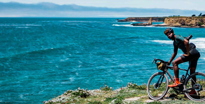a person riding a bicycle next to a body of water: Get Unlimited Access to Bicycling.com