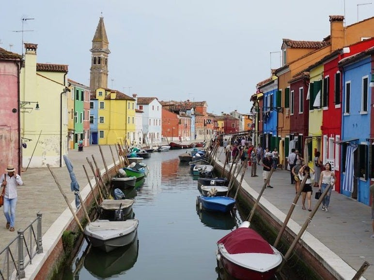"""Slide 4 of 15: Burano was the first trip Teso made post-lockdown.""""It's a world apart from Venice,"""" Teso said.Burano is an island in the Venetian lagoon, and it's well known for its artists and lace makers. Shops are sprinkled along the town's canals, where women are embroidering everything from tablecloths to wedding dresses.But the island is also popular for its colorful buildings. The streets are filled with bright pinks, blues, yellows, and purples — there's even a law that requires residents to paint their homes with bold colors.Teso said that the city can get crowded during the day, with tourists visiting from Venice. But at night, the entire town is calm.That's because Burano is often seen as a day-trip destination for visitors, and they typically leave before sunset.Teso recommends taking a boat tour, eating delicious seafood, and exploring the island's lace museum."""