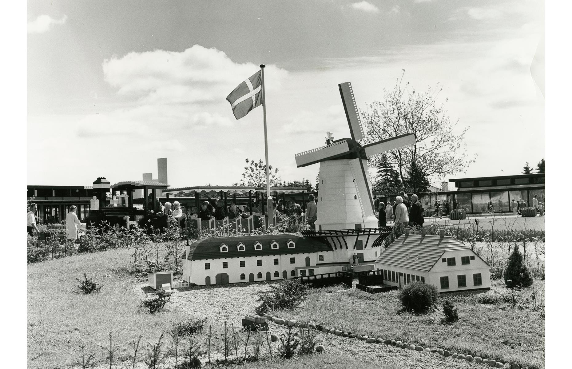 Slide 20 of 35: From the very beginning, Legoland's intricate models made from rainbow blocks pleased visitors. In this picture from 1968, guests marvel at a Lego replica of Denmark's Dybbøl Mølle windmill as the Lego train rumbles along in the background.