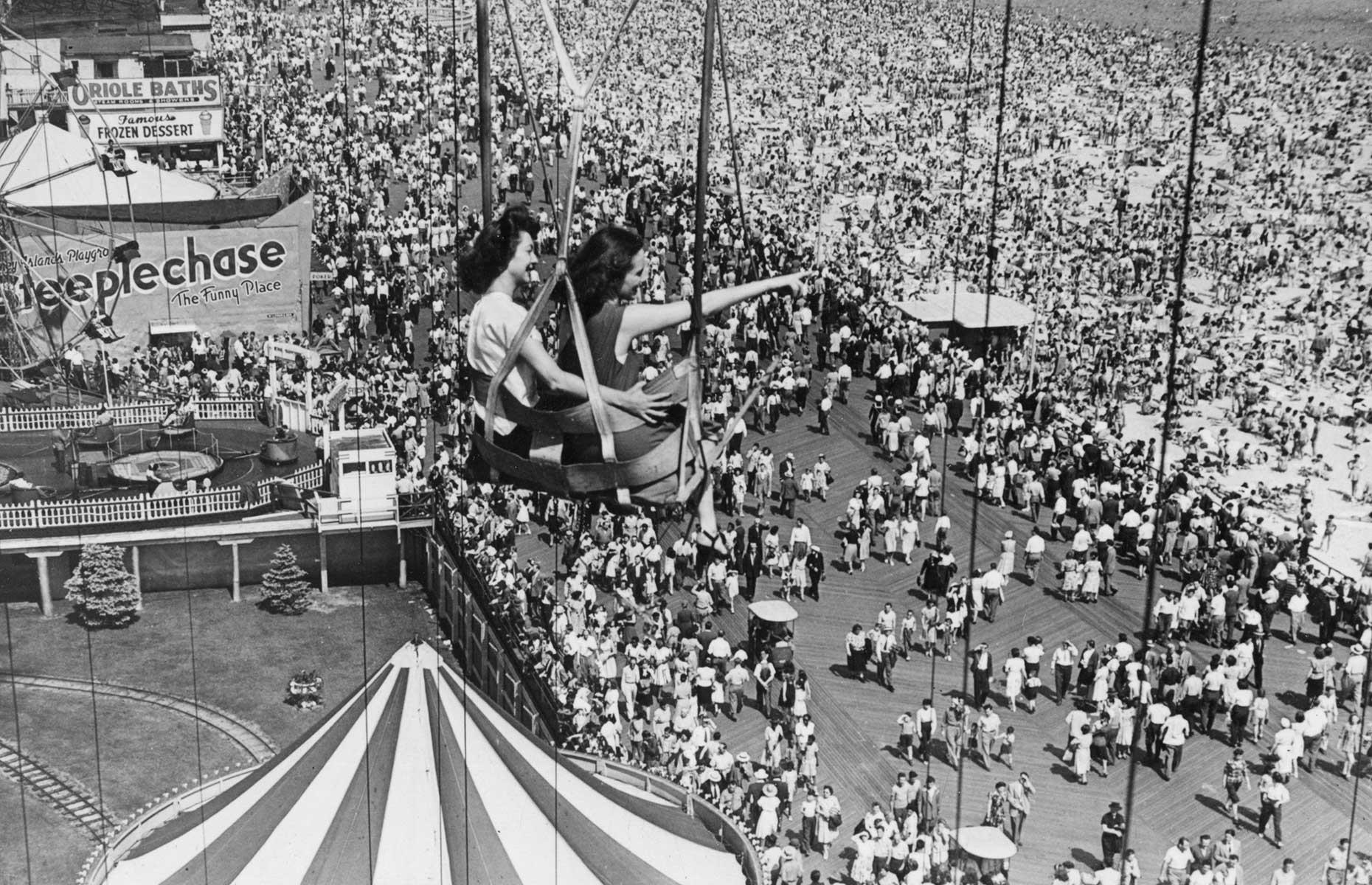 Slide 3 of 35: Coney Island continued to boom through the first half of the 20th century, with its seaside location, colorful attractions and daring rides the perfect mix for pleasure seekers. You can barely see the beach or the boardwalk for people in this 1946 shot, which also shows beaming vacationers on Coney's now defunct Parachute Jump ride.