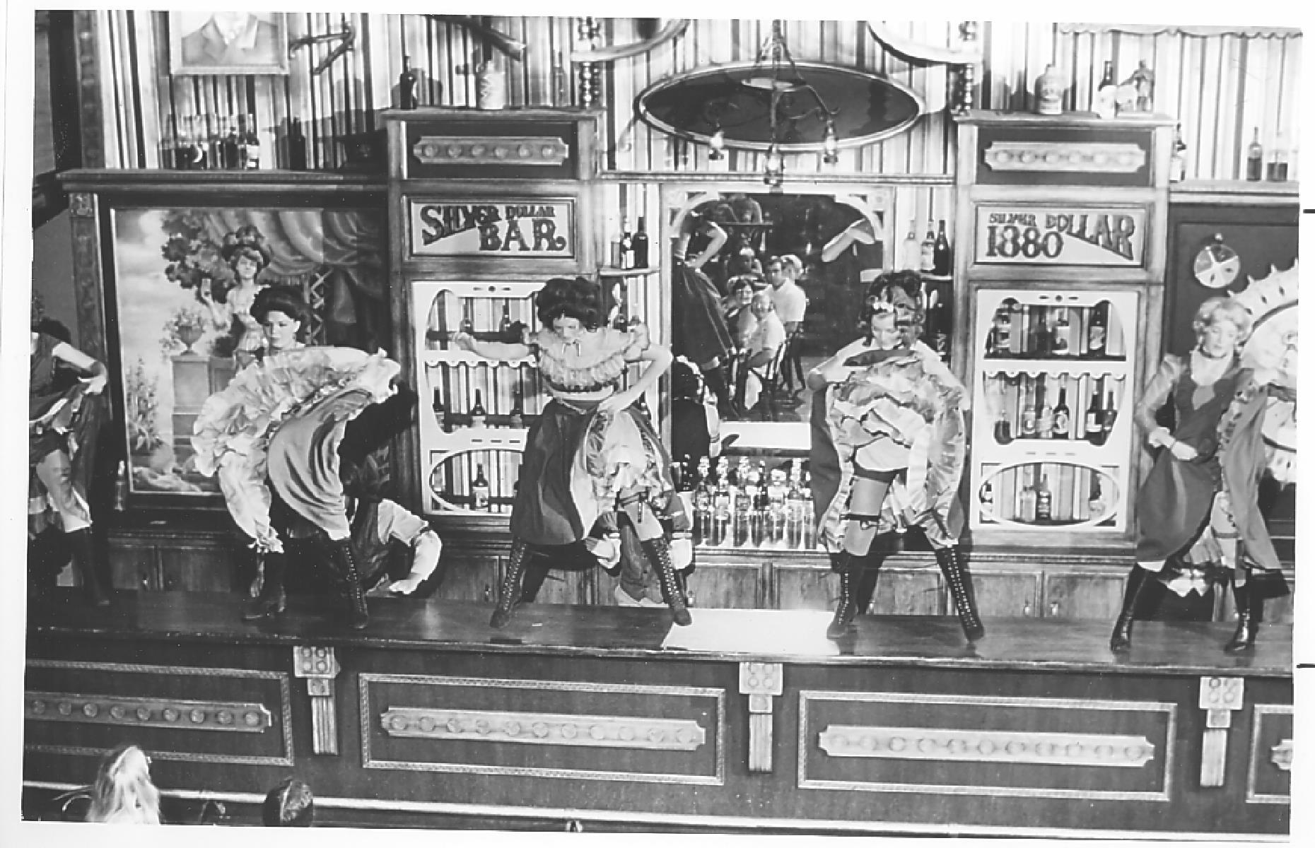 Slide 17 of 35: Alongside the carefully curated Old West-style attractions, visitors to the park could expect plenty of live entertainment. Pictured here is a stomping saloon show in the Silver Dollar Bar – look carefully and you can see the faces of delighted audience members in the mirror.