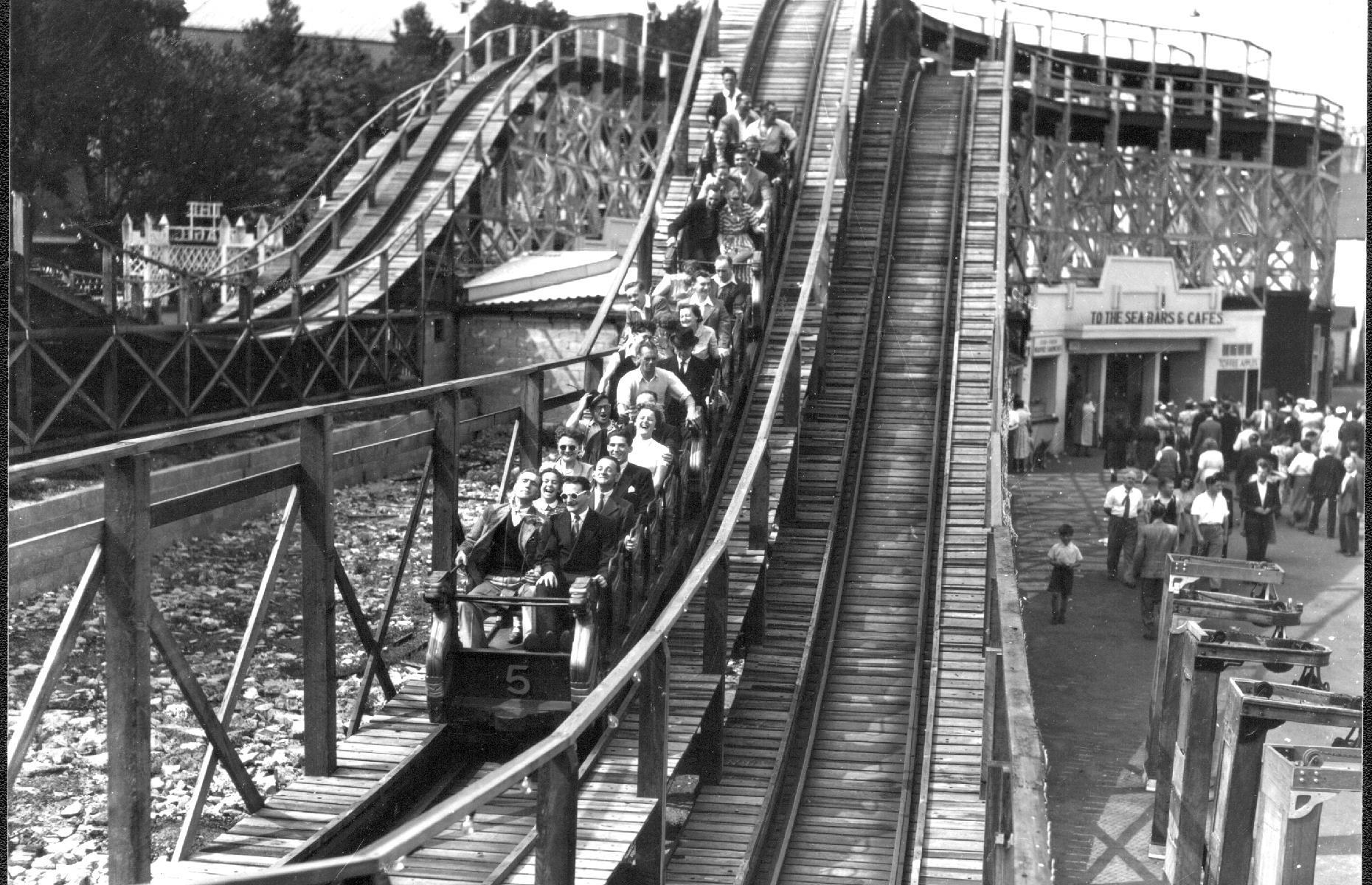 Slide 30 of 35: It was in the 1920s, however, that the park began to take its modern shape. The Scenic Railway – a wooden coaster finished in 1920 – helped seal the park's success for years to come. It was badly damaged in the fire of 2008, but has once again been restored and remains a Grade II-listed structure. It's pictured in action during the 1930s. Check out other exciting roller coasters from around the world too.