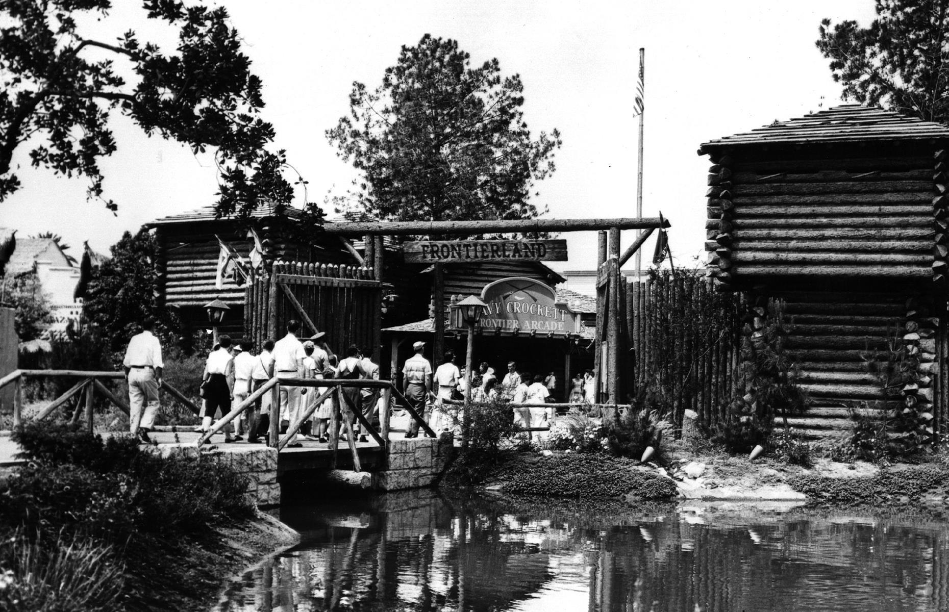 Slide 32 of 35: Another of Disneyland's enduring attractions is Frontierland, an Old West-themed land that has been part of the park from the very beginning. Here tourists are seen crossing the waters into a land of saloons, cowboys, pirates and pioneers, with early attractions including the Mark Twain Riverboat, which still plows the park's waters today. This photograph was snapped around 1955, not long after the park's opening date.