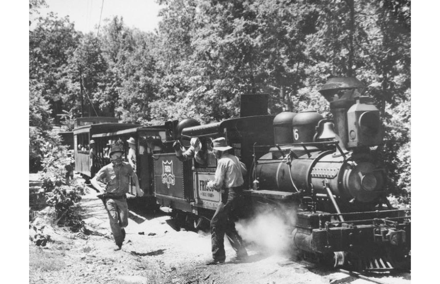 Slide 18 of 35: By the 1960s, one of Silver Dollar City's top attractions had been added: a steam train (pictured) that chugs through the leafy Ozarks countryside. But beware: along the way passengers would be (and still are) held up by train robbers that emerged from the woods ready to loot and plunder.