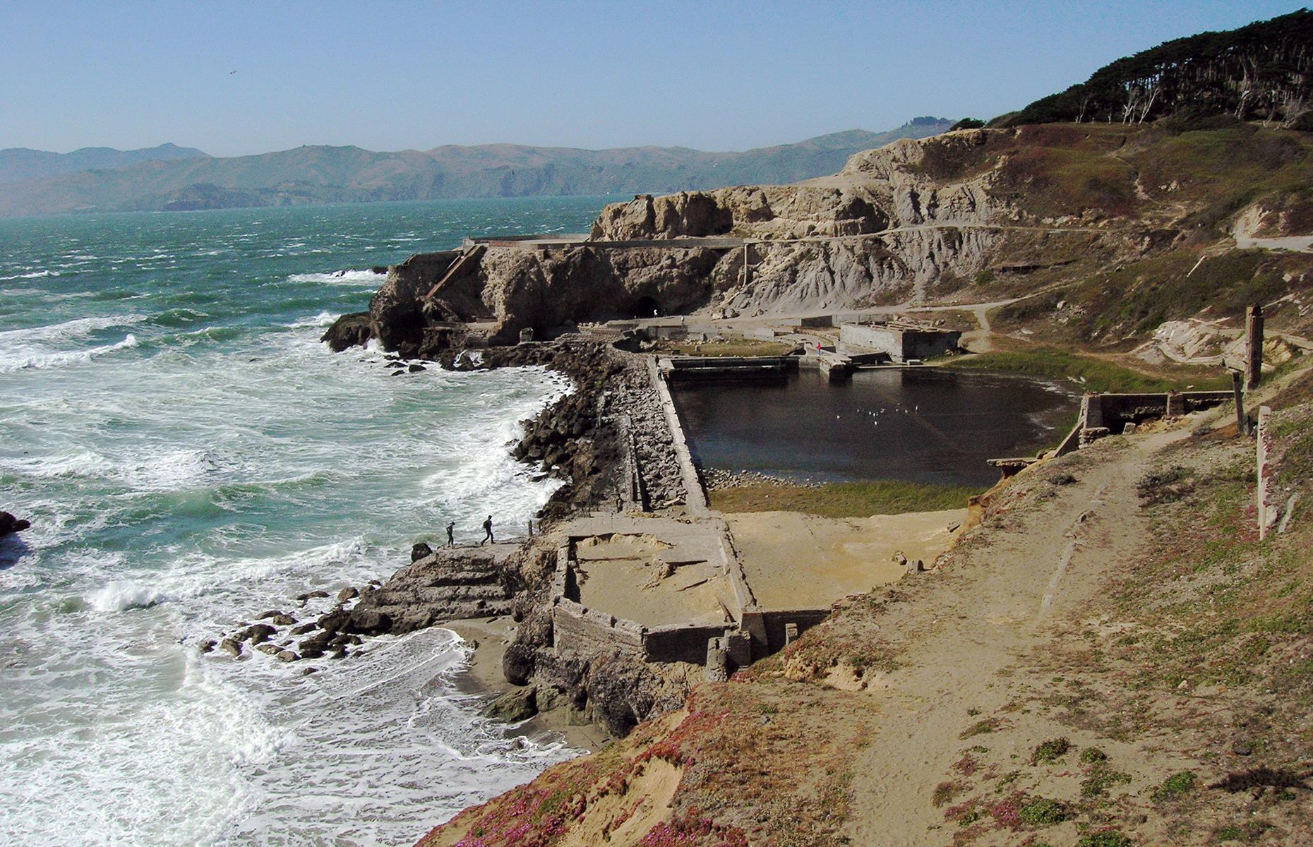 Slide 11 of 39: After struggling financially for many years, the Sutro Baths closed in 1966, and later burned down in June that same year. Now, just the foundations remain as a reminder of the Victorian attraction, with the cliffside setting making the site a popular spot for walkers.